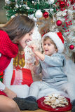 Happy son and mother eating Christmas cookies. Cheerful son sitting under Christmas tree and feeding his mother with Christmas cookies Royalty Free Stock Photography