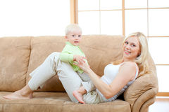Happy son and mother lying on sofa Stock Image