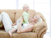 Happy son and mother playing on sofa. In living room royalty free stock images