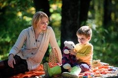 Happy son with mother relax in autumn forest. Sunny weather. Healthy food. Mother love small child. Spring mood. Happy. Family day. Family picnic. Mothers day royalty free stock image
