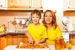 Happy son and mother slicing pizza in the kitchen Stock Photography