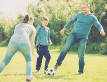 Happy son and parents playing football. In grass field Royalty Free Stock Images