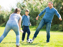 Happy son and parents playing football. In grass field Stock Photos