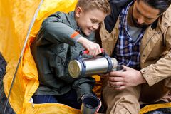 Son with thermos in camping. Happy son pouring hot drink from thermos to fathers cup white sitting in camping tent royalty free stock photo