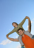 Happy son on the shoulders of the father Stock Photos