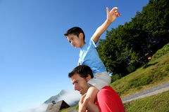 Happy son on the shoulders of his father Stock Image