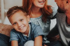 Happy son sitting on bed together with parents stock photos