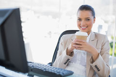 Happy sophisticated businesswoman holding coffee. In bright office royalty free stock photo