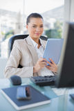 Happy sophisticated businesswoman holding tablet pc. In bright office Stock Photography