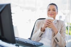 Happy sophisticated businesswoman smelling coffee. In bright office Stock Photography