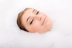 Happy spa: beautiful attractive young woman brunette girl having fun in the foam enjoying eyes closed, closeup portrait Stock Photography