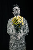 Happy spaceman with flowers. Portrait of happy spaceman holding flowers and looking up Stock Images