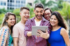 Happy spanish hipster student with tablet computer and group of cheering international students royalty free stock photos