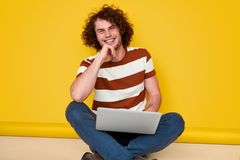 Cheerful coder smiling for camera. Happy IT specialist smiling and looking at camera while using laptop against yellow background stock photography