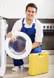 Happy specialist with tooling near washing machine Stock Images