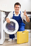 Happy specialist with tooling near washing machine Stock Photography