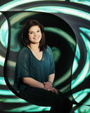 Happy in a Spiral. Portrait of a beautiful young teen sitting in a teal-colored spiral on black Stock Images
