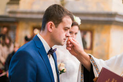 Happy spiritual groom kissing wedding ring at ceremony in church Stock Images