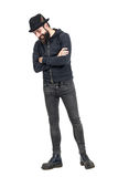 Happy spontaneous laughing hipster with fedora hat looking down. Full body length portrait isolated over white studio background royalty free stock image