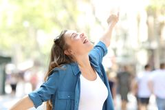 Happy spontaneus woman stretching arms. Celebrating success in the street Stock Images