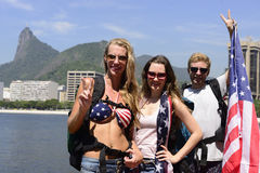 Happy sport fans holding USA Flag in Rio de Janeiro, Brasil. Sport fans holding USA Flag in Rio de Janeiro with Christ the Redeemer in background Stock Photos