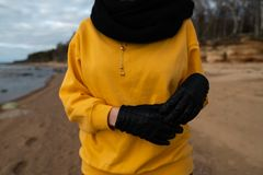 Happy sport and fashion lover enthusiast working out on a beach wearing bright yellow sweater and black gloves and a cap stock photo
