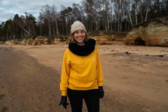 Happy sport and fashion lover enthusiast working out on a beach wearing bright yellow sweater and black gloves and a cap royalty free stock images