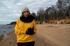 Happy sport and fashion lover enthusiast working out on a beach wearing bright yellow sweater and black gloves and a cap stock photography