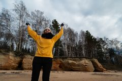 Happy sport and fashion lover enthusiast working out on a beach wearing bright yellow sweater and black gloves and a cap stock images