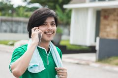 Male using mobile phone calling while exercising. Happy sport male using mobile phone calling while exercising Stock Images