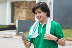 Male using mobile phone while exercising. Happy sport male using mobile phone while exercising Royalty Free Stock Photo