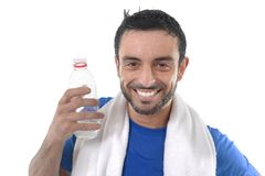 Happy sport man posing corporate with water and towel for fitness center. Young happy and attractive sport man sweaty after intense training with towel around stock photography