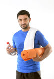 Happy sport man posing with water and mat for fitness center add Royalty Free Stock Photos