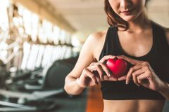 Happy sport woman holding red heart in fitness gym club. Medical cadio heart strength training lifestyle. Pretty female sport girl royalty free stock photos