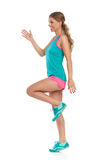Happy Sport Woman Standing Tiptoe On One Leg. Happy beautiful young woman in pink shorts, green tank top and sneakers standing tiptoe on one leg and looking away Royalty Free Stock Photos