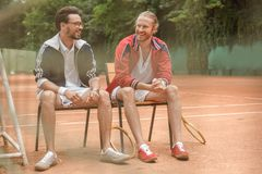 happy sportive friends with wooden rackets sitting on chairs royalty free stock image