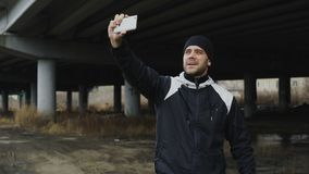 Happy sportive man taking selfie portrait with smartphone after training in urban outdoors location in winter stock video