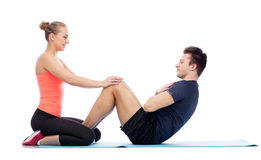 Happy sportive man and woman doing sit-ups. Sport, fitness, lifestyle and people concept - happy sportive men and women doing sit-ups Royalty Free Stock Photography