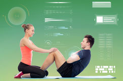 Happy sportive man and woman doing sit-ups. Sport, fitness, technology and people concept - happy sportive men and women doing sit-ups Stock Photo
