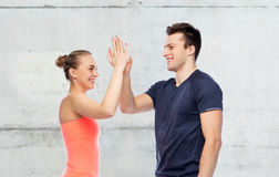 Happy sportive man and woman making high five Royalty Free Stock Photos