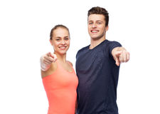 Happy sportive man and woman pointing finger. Sport, fitness, lifestyle and people concept - happy sportive men and women pointing finger on you Royalty Free Stock Images