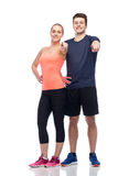 Happy sportive man and woman pointing finger. Sport, fitness, lifestyle and people concept - happy sportive men and women pointing finger on you Stock Image