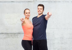 Happy sportive man and woman pointing finger Royalty Free Stock Photo