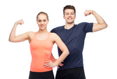 Happy sportive man and woman showing biceps power. Sport, fitness, power, strength and people concept - happy sportive men and women showing biceps Royalty Free Stock Photos