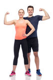 Happy sportive man and woman showing biceps power. Sport, fitness, power, strength and people concept - happy sportive men and women showing biceps Stock Image