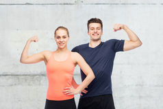 Happy sportive man and woman showing biceps power. Sport, fitness, power, strength and people concept - happy sportive men and women showing biceps over concrete Stock Photo