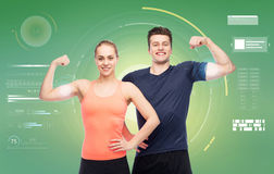 Happy sportive man and woman showing biceps power. Sport, fitness, power, technology and people concept - happy sportive men and women showing biceps over green Royalty Free Stock Photos