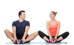Happy sportive man and woman sitting on mats Stock Photos