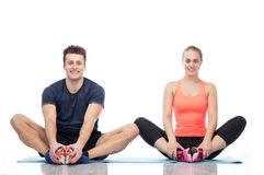 Happy sportive man and woman sitting on mats Stock Image