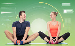 Happy sportive man and woman sitting on mats. Sport, fitness, technology and people concept - happy sportive men and women sitting on mats over green background Stock Image